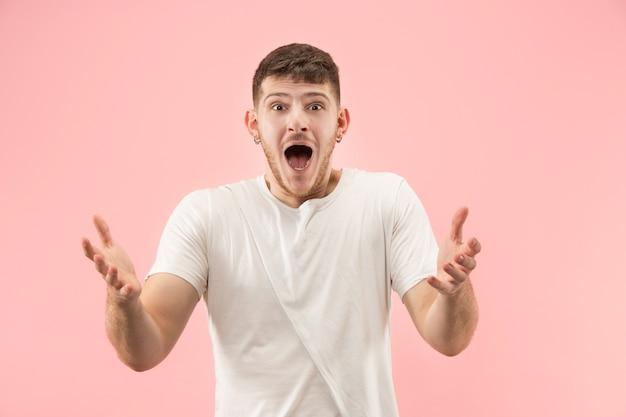 Młody atrakcyjny mężczyzna szuka zaskoczony na białym tle na różowo