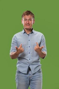 Młody atrakcyjny mężczyzna szuka zaskoczony na białym tle na zielono