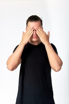 Młody atrakcyjny mężczyzna ukrywa oczy rękami i uśmiecha się