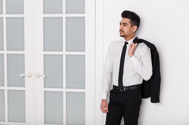 Młody atrakcyjny mężczyzna w białej koszuli, krawacie i kurtce wisi na ramieniu.