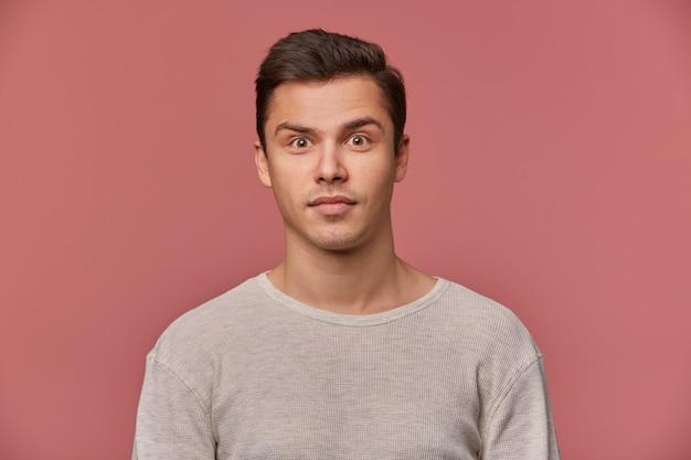 Młody atrakcyjny mężczyzna w pustym longsleeve, spokojnie patrzy w kamerę, stoi na różowym tle.