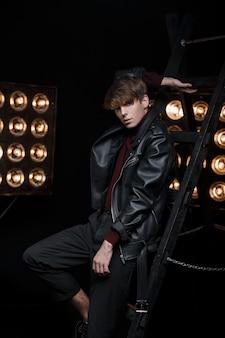 Młody atrakcyjny mężczyzna w stylowej skórzanej kurtce w stylu retro w dżinsach i golfie pozowanie w studio w pobliżu metalowych schodów na tle jasnych pomarańczowych lamp vintage. stylowy seksowny facet