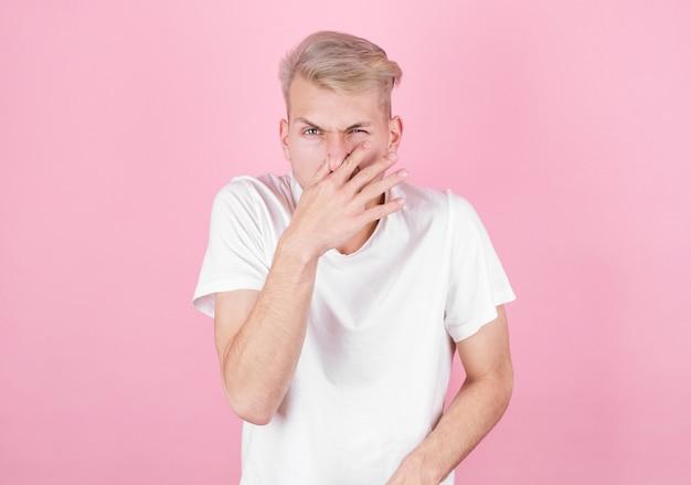 Młody atrakcyjny mężczyzna z obrzydzeniem na twarzy szczypie nos, coś śmierdzi, na różowym tle. wyraz twarzy negatywnych emocji.