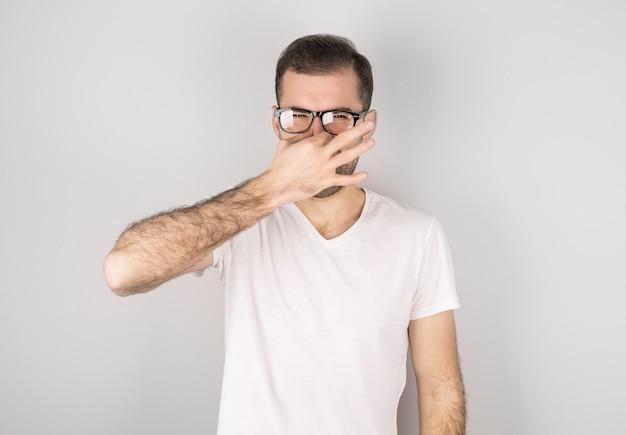 Młody atrakcyjny mężczyzna z obrzydzeniem na twarzy szczypie nos, coś śmierdzi, na szarym tle. wyraz twarzy negatywnych emocji.