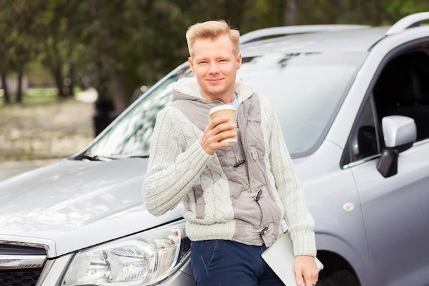 Młody atrakcyjny mężczyzna z papierową filiżanką kawy w samochodzie