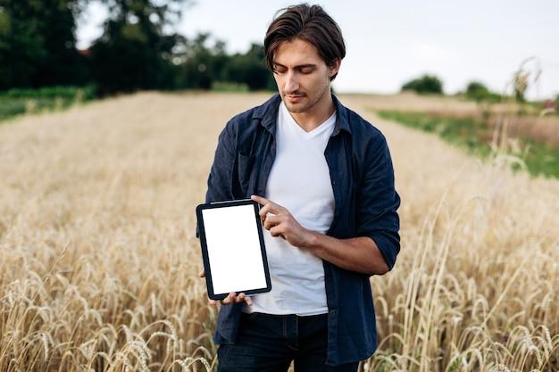 Młody, atrakcyjny mężczyzna z tabletem w dłoniach na polu pszenicy