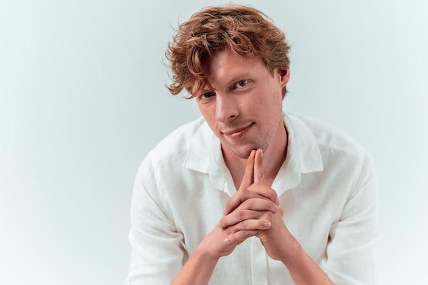 Młody atrakcyjny mężczyzna złożone ręce. kaukaski rudowłosy facet w białej koszuli na białym tle
