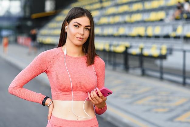 Młody atrakcyjny model fitness słuchanie muzyki na smartfonie charching pozytywną energię przed treningiem na zewnątrz.