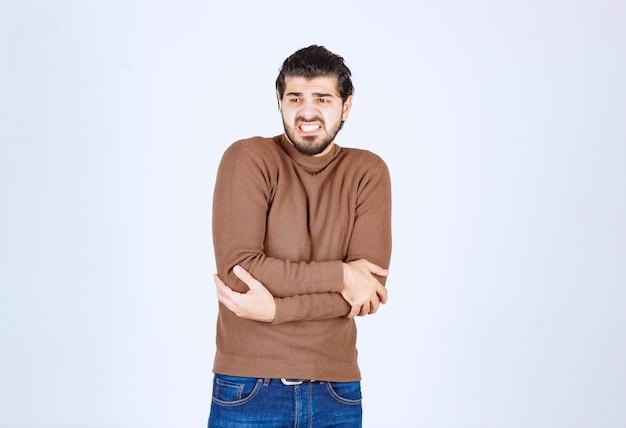 Młody atrakcyjny model w brązowym swetrze robi gesty na białej ścianie.