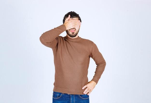 Młody atrakcyjny model w brązowym swetrze zasłaniając twarz na białej ścianie.