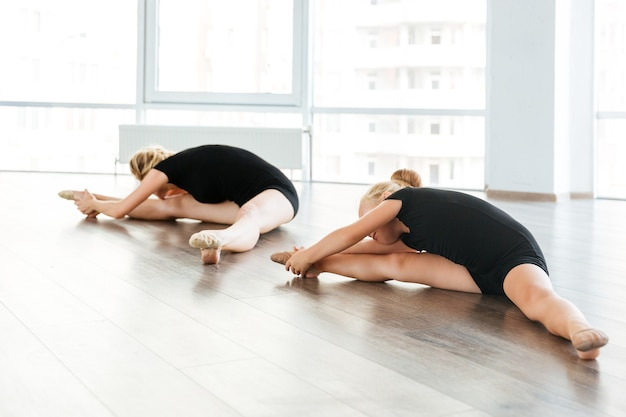 Młody atrakcyjny nauczyciel baletu i jej mały uczeń robi ćwiczenia na podłodze w studio