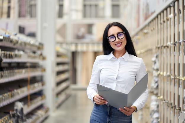 Młody atrakcyjny pozytywny dziewczyna sprzedawca na tle centrum handlowe