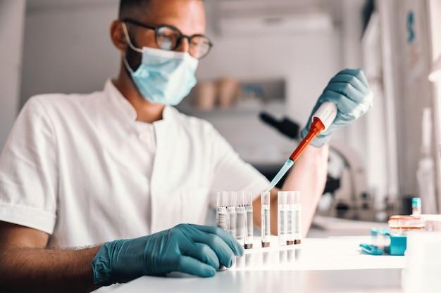 Młody atrakcyjny pracownik medyczny robi badania nad szczepionką przeciw wirusowi corna, siedząc w laboratorium.