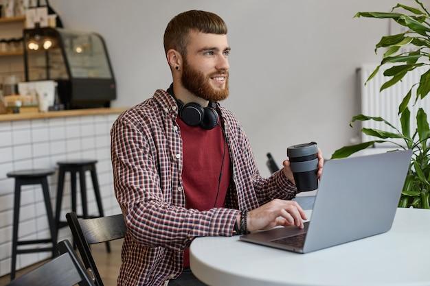 Młody atrakcyjny rudy brodaty mężczyzna pracuje przy laptopie, siedzi w kawiarni i pije kawę, szeroko uśmiechając się i ciesząc się z pracy, odwracając wzrok w oczekiwaniu na sukces, nosząc podstawowe ubrania.