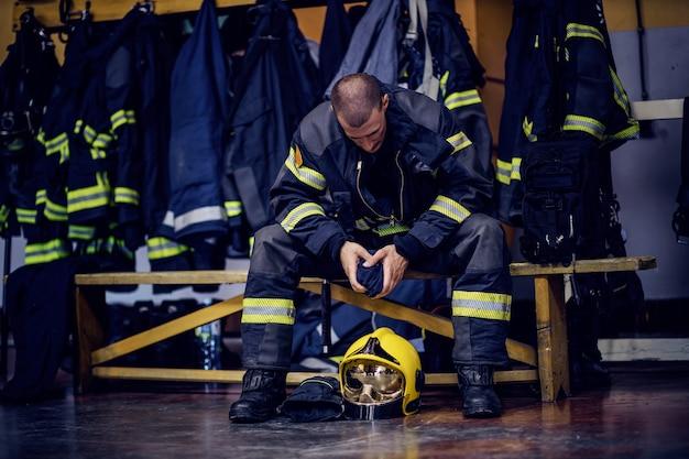 Młody atrakcyjny strażak w mundurze ochronnym siedzi w remizie.