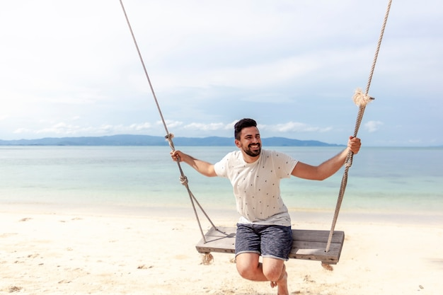 Młody atrakcyjny szczęśliwy mix ścigał się mężczyzna kołysząc się na huśtawce na brzegu jasnego morza tropikalnego