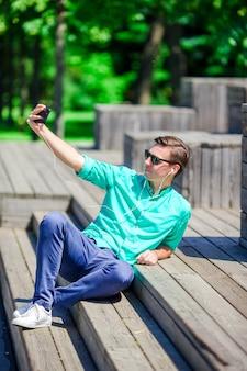 Młody atrakcyjny turysta bierze selfie fotografię z telefonem komórkowym outdoors cieszy się wakacje podróży miejsce przeznaczenia w turystyce.