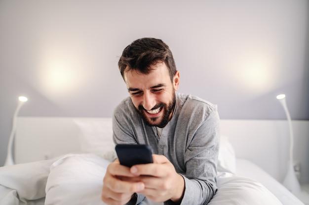 Młody atrakcyjny uśmiechnięty brodaty mężczyzna siedzi na łóżku w sypialni i za pomocą inteligentnego telefonu do późnej nocy na czacie online ze swoją dziewczyną