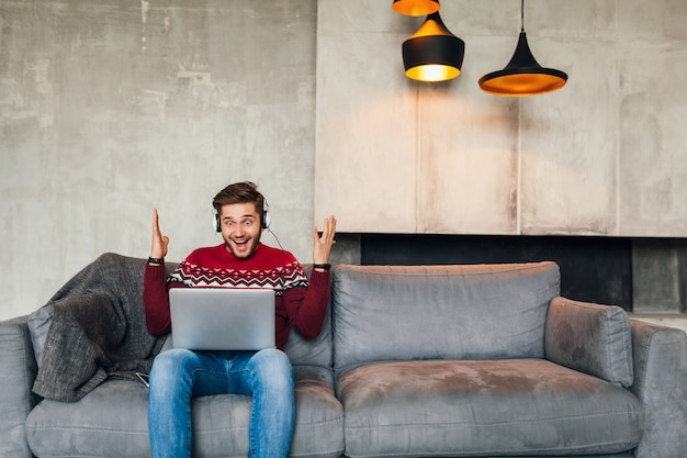 Młody atrakcyjny uśmiechnięty mężczyzna siedzi na kanapie w domu zimą z zaskoczonym wyrazem twarzy, ubrany w czerwony sweter z dzianiny, pracuje na laptopie, freelancer, emocjonalny, krzyczy, słucha słuchawek