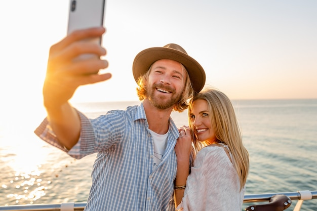 Młody atrakcyjny uśmiechnięty szczęśliwy mężczyzna i kobieta podróżuje na rowerach, biorąc zdjęcie selfie na aparat telefoniczny, romantyczna para nad morzem o zachodzie słońca, strój w stylu boho hipster, przyjaciele bawią się razem