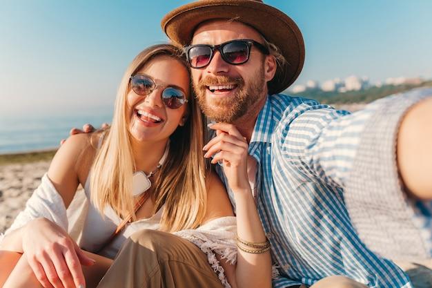 Młody atrakcyjny uśmiechnięty szczęśliwy mężczyzna i kobieta w okularach przeciwsłonecznych, siedząc na piaszczystej plaży, biorąc zdjęcie selfie