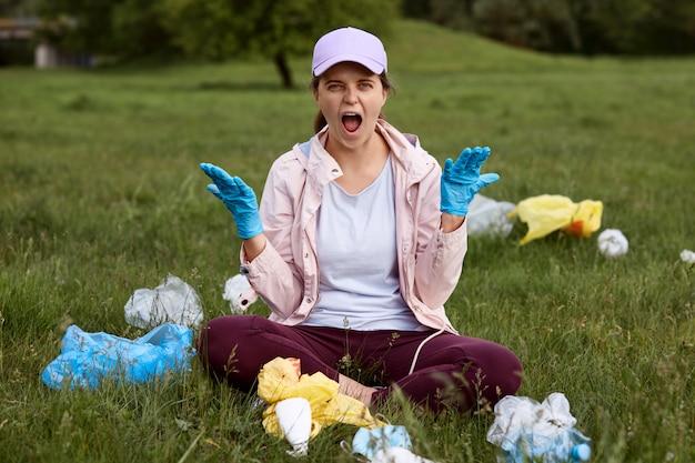 Młody atrakcyjny wolontariusz siedzi w środku, jeśli łąka i krzyczy z rozpaczy