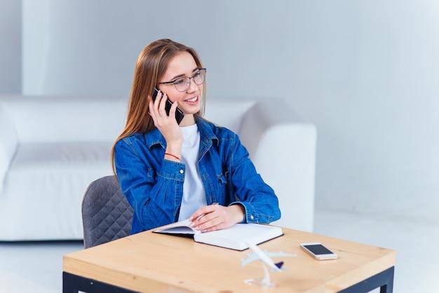 Młody atrakcyjny żeński uczeń używa smartphone podczas gdy studiujący w domu.