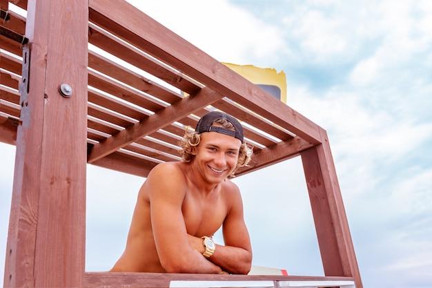 Młody attceractive faceta surfingowiec stoi na tarasie szkoły surfingu patrzeje kamerę