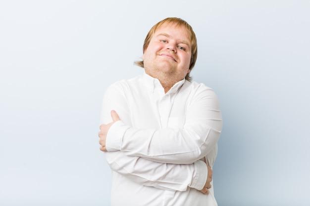 Młody autentyczny gruby mężczyzna przytula, uśmiecha się beztrosko i szczęśliwy.