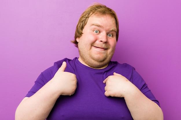 Młody autentyczny gruby mężczyzna zaskoczył wskazując palcem, uśmiechając się szeroko.