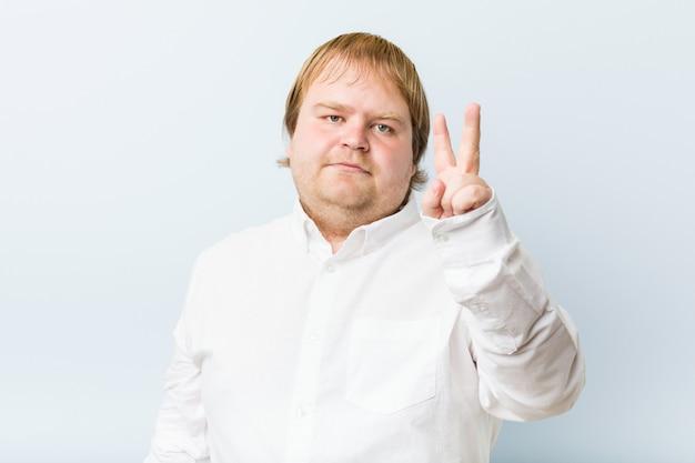 Młody autentyczny rudzielec mężczyzna pokazuje numer dwa z palcami.