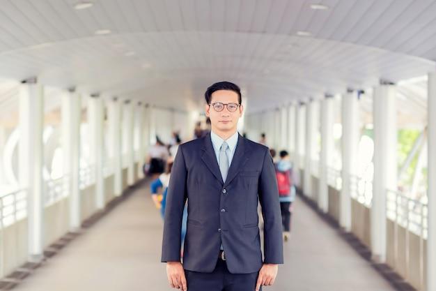 Młody azja przystojny biznesmen stoi na przejściu nowożytny miasto z jego szkłami.