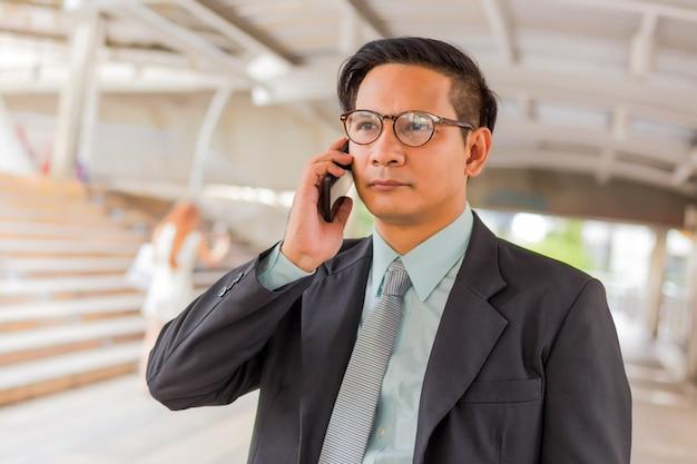 Młody azja przystojny biznesmen z jego smartphone pozycją na przejściu nowożytny miasto.
