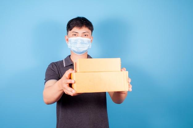 Młody azjata noszący maskę dostarcza pudła z przesyłkami ekspresowymi na niebieskim tle