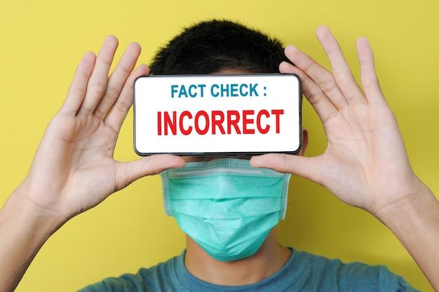 """Młody azjata noszący maskę ochronną, na ekranie telefonu wyświetla się tekst """"weryfikacja faktów: nieprawidłowy"""". niepoprawne informacje o epidemii koronawirusa."""