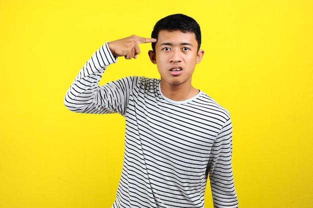 Młody azjata robi gest szaleństwa kładąc palec na głowie, odizolowany na żółtym tle