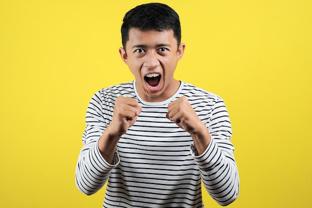 Młody azjata robi zły gest, zirytowany i emocjonalny, odizolowany na żółtym tle