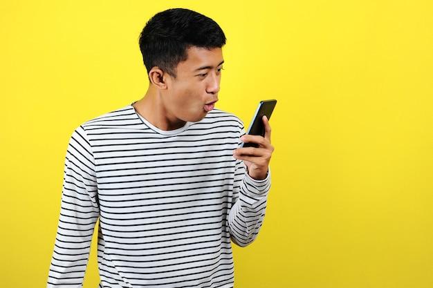 Młody azjata rozmawia zły przed swoim telefonem z ekranem
