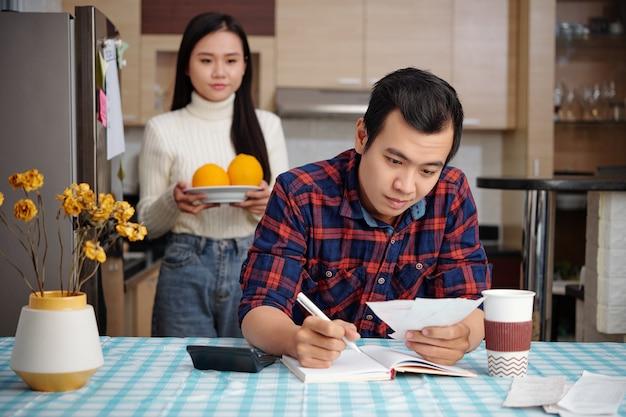Młody azjata spisuje dochody i wydatki, próbując kontrolować domowe finanse