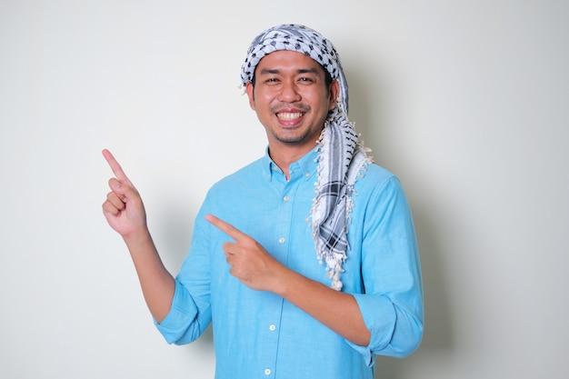 Młody azjata ubrany w arabską chustę shemagh wskazującą na bok