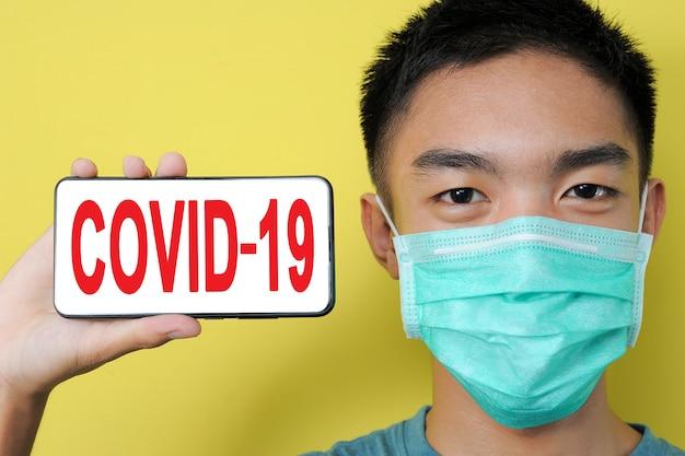 Młody azjata ubrany w maskę ochronną pokazujący tekst covid-19 na ekranie telefonu obok głowy, na białym tle na żółtym tle