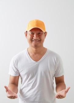 Młody azjata ubrany w pomarańczową czapkę na jasnoszarej ścianie