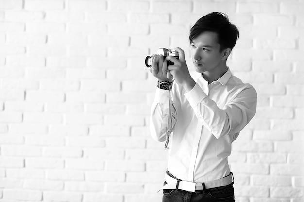 Młody azjata używa aparatu w studio