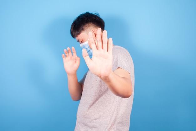 Młody azjata w masce podniósł rękę, nie zbliżając się. aby zapobiec covid-19