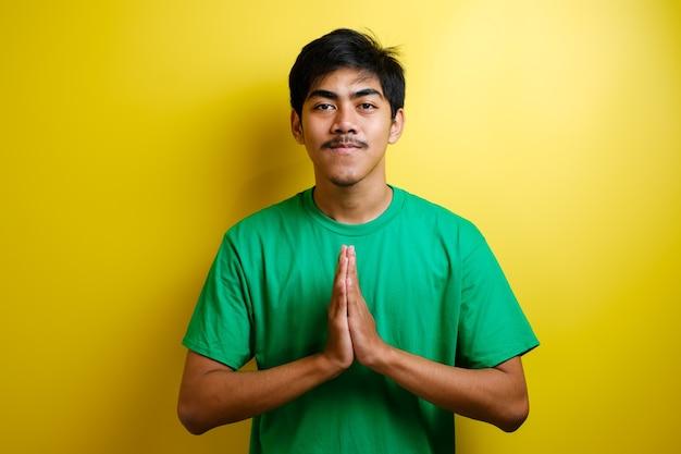 Młody azjata w zielonej koszulce uśmiecha się i pokazuje azjatycki gest powitania na żółtym tle
