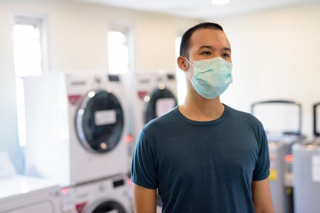 Młody azjata z maską do ochrony przed wybuchem koronawirusa w pralni w pomieszczeniu