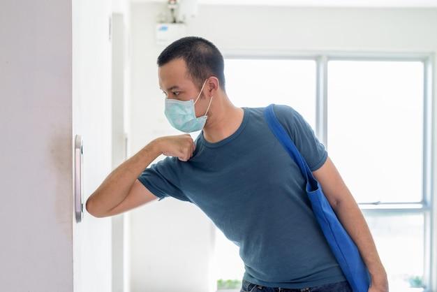 Młody azjata z maską naciskając przycisk windy łokciem, aby zapobiec rozprzestrzenianiu się koronawirusa
