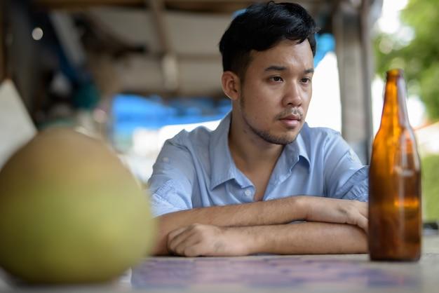Młody azjatycki alkoholik pije piwo na ulicach na zewnątrz