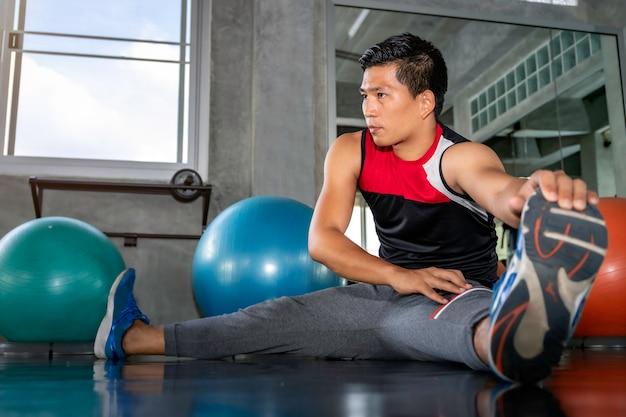 Młody azjatycki atrakcyjny mężczyzna rozciąganie przy sprawności fizycznej gym.
