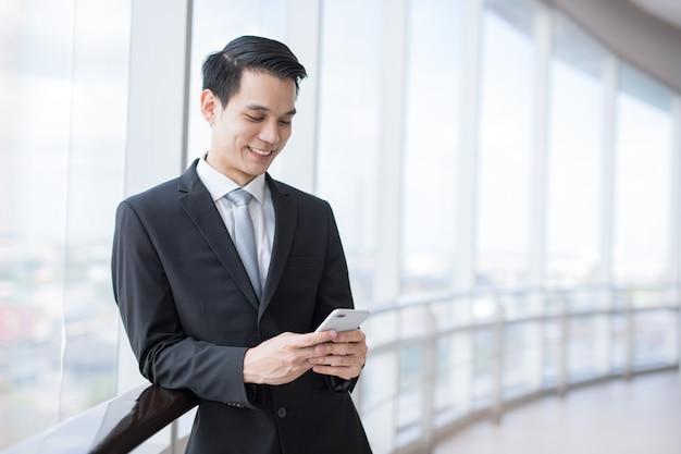 Młody azjatycki biznes człowiek uśmiech trzyma inteligentny telefon w biurze areaman inteligentna koncepcja biznesowa